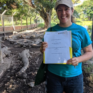 Lauren Augustine holding the Memorandum of Agreement between the Saint Louis Zoo WildCare Institute, the Enterprise for the Conservation of the Zapata Swamp, Zapata Crocodile Farm.